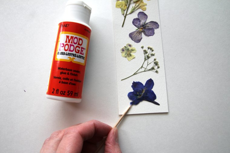 gluing flowers down with Mod Podge
