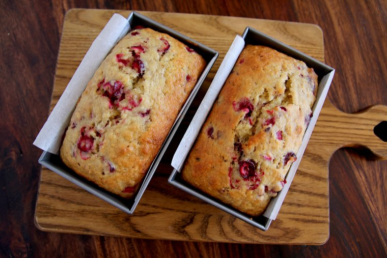 two loaves of cranberry banana bread on a cutting board