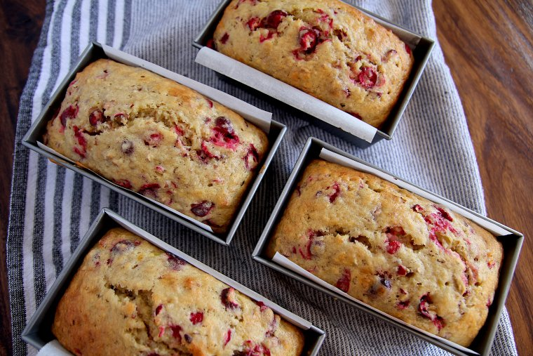 four loaves of cranberry banana bread on a kitchen towel