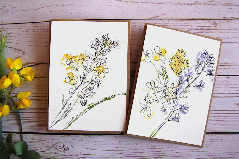two hammered flower greeting cards on a table next to yellow wildflowers