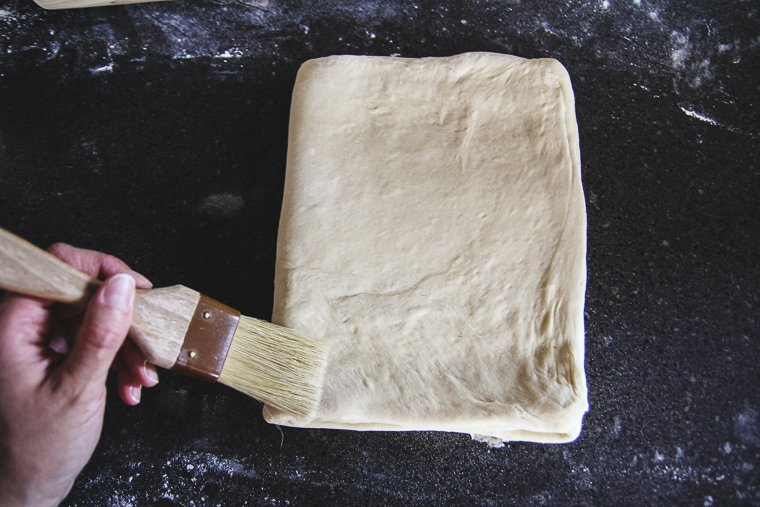 folding the dough in thirds as if folding a letter, brushing away loose flour