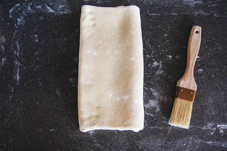 folding the folded ends of the dough together as if closing a book to finish the first lamination fold
