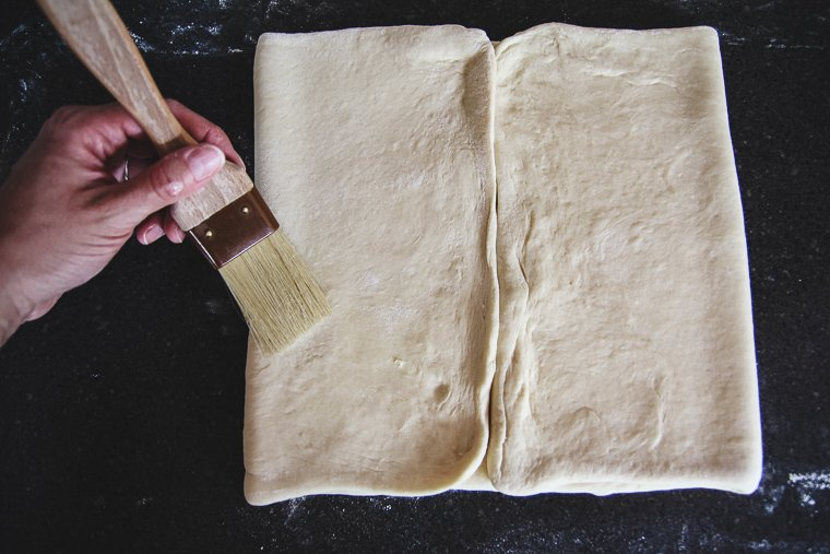 folding the edges of the dough to meet in the middle, brushing away extra flour as I go