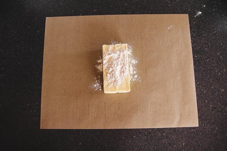 cold butter and flour on a sheet of parchment paper