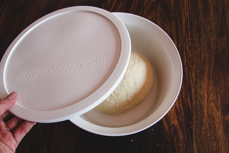 placing dough in a lidded bowl for fermentation