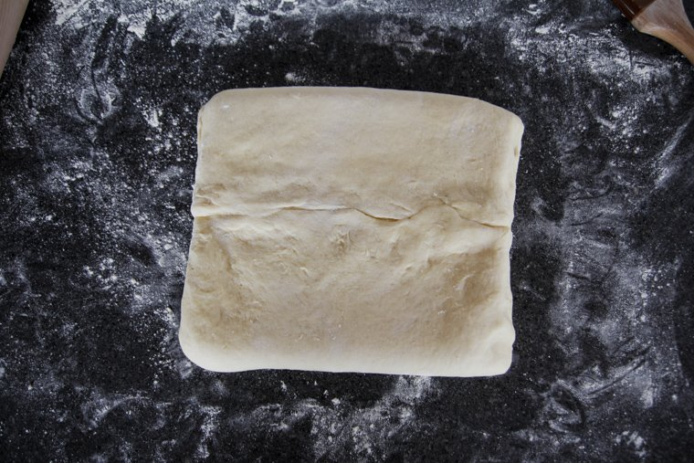 Dough rotated sideways with the center seam horizontal to the person rolling the dough