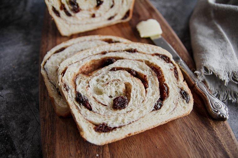 sourdough cinnamon raisin bread on a cutting board, up close