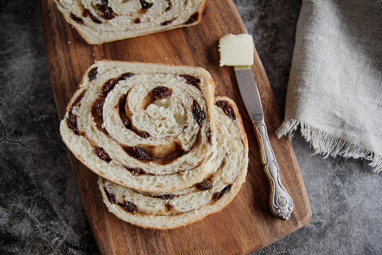 two slices of sourdough cinnamon raisin bread with a table knife and a pat of butter