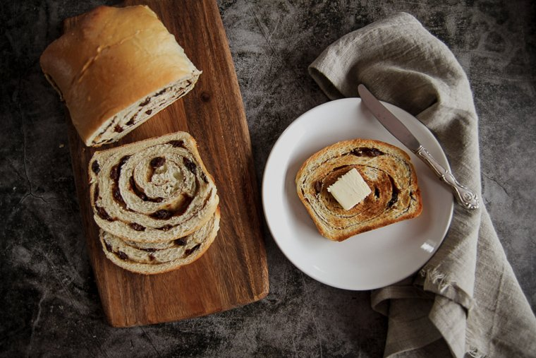a cutting board with sliced sourdough cinnamon raisin bread next to a place with a slice toasted and buttered