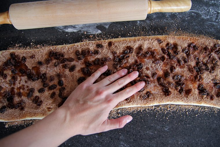 pressing soaked raisins into the dough