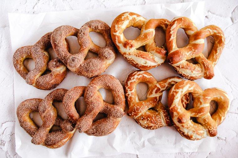 8 sourdough soft pretzels arranged on a piece of white parchment paper