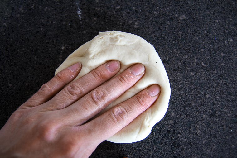degassing a piece of dough to begin preshaping