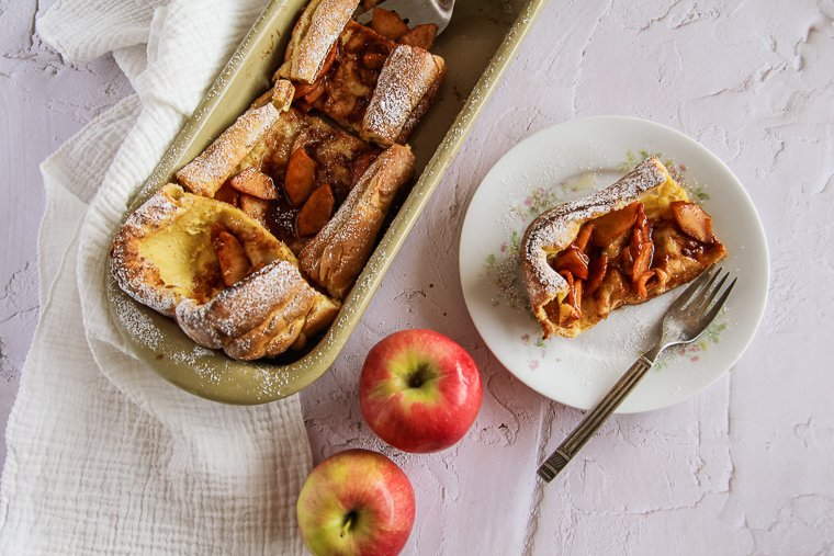 A sliced German apple pancake sitting next to two red apples